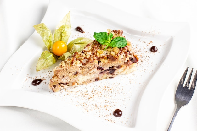The piece of cake with nuts, dried fruits and physalis on white plate