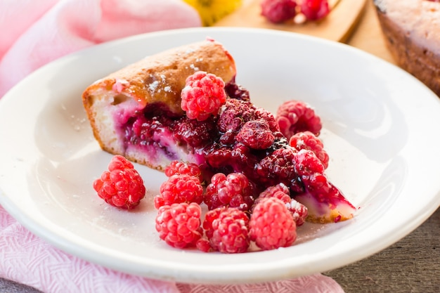 A piece of cake with raspberries and fresh berries on the plate