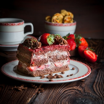 Piece of cake with strawberry and crumbs and cup of tea in plate