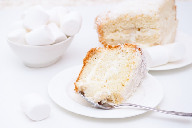 Piece of cake with white cream and coconut chips and marshmallows