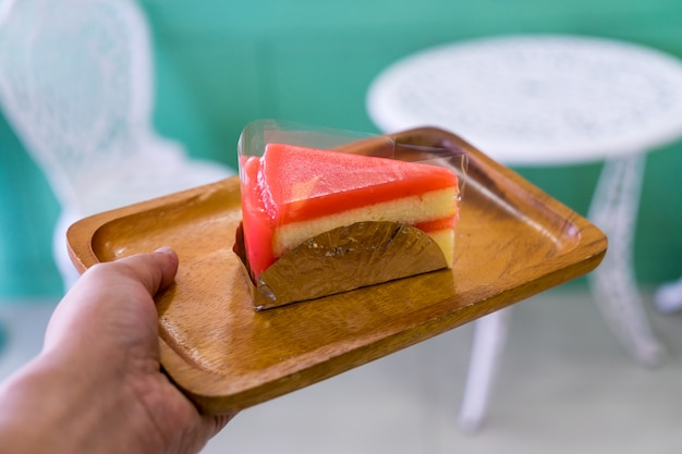 Piece of cake on wood plate on han