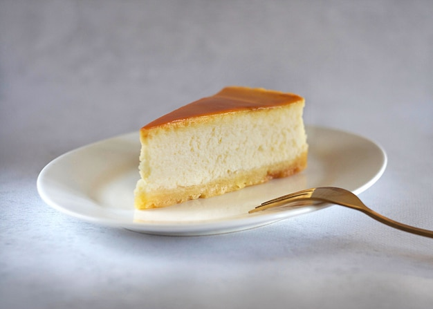 A piece of caramel cheesecake on a saucer on the table with a gold fork next to it.