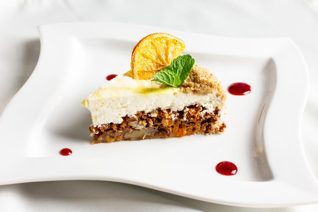 The piece of carrot cake with cream, nuts and dried orange on white plate