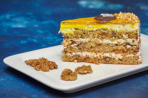 Piece of carrot cake with icing and walnut on plate