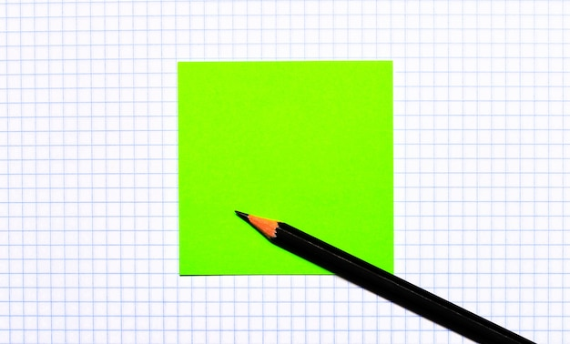 On a piece of checkered paper there is a green note sticker and a black pencil. copy space.