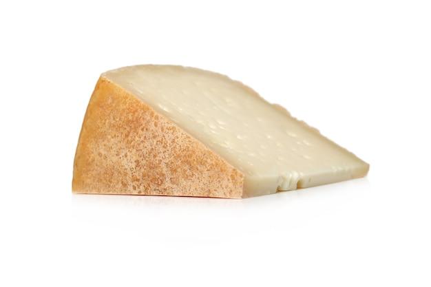 Pezzo di formaggio su una superficie bianca