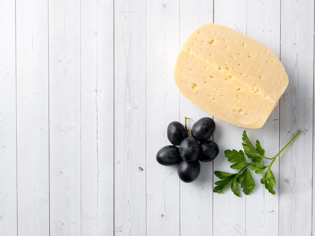 Piece of cheese with parsley and red grapes on white wooden background