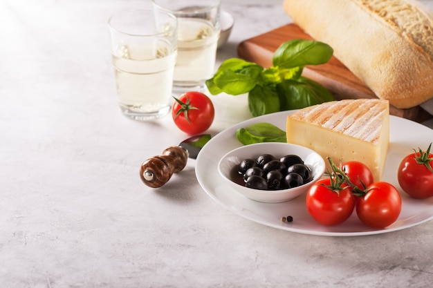 Piece of cheese with tomatoes and black olives on a plate