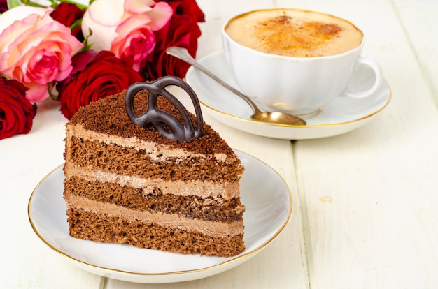 Piece of chocolate cake, cappuccino, flowers on table.