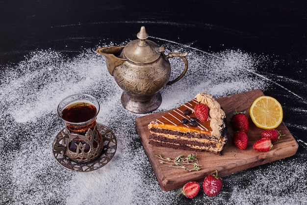 A piece of chocolate cake decorated with fruits on dark background with classic tea set .