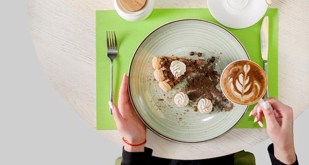 A piece of chocolate cake decorated with meringues, coffee beans and biscuit crumbs, holding a cappuccino in hand. dessert tiramisu , top view.