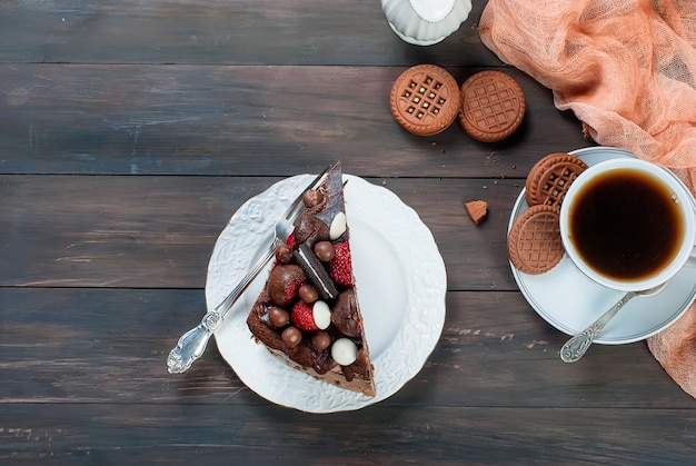 Piece of chocolate cake on a plate and a cup of coffee