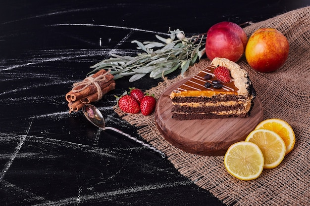 A piece of chocolate cake on round wooden plate with cinnamon and various fruits.