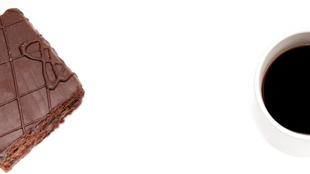 A piece of chocolate cake on a white isolated background next to it is a cup with a hot drink