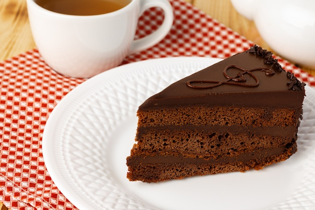 Piece of chocolate cake on white plate on table