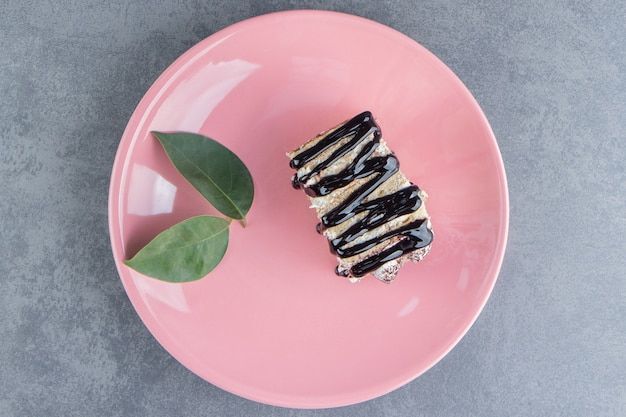 Un pezzo di torta al cioccolato con foglia su un piatto rosa