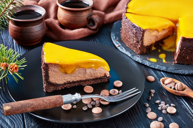 A piece of a chocolate mango cheesecake served on a black plate with dessert fork and chocolate chips. fir tree and cups with coffee on a wooden table, view from above,  close-up