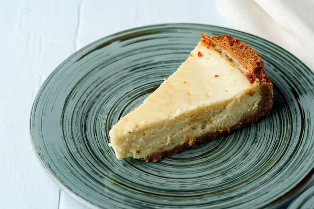 Piece of classic cheesecake on green plate