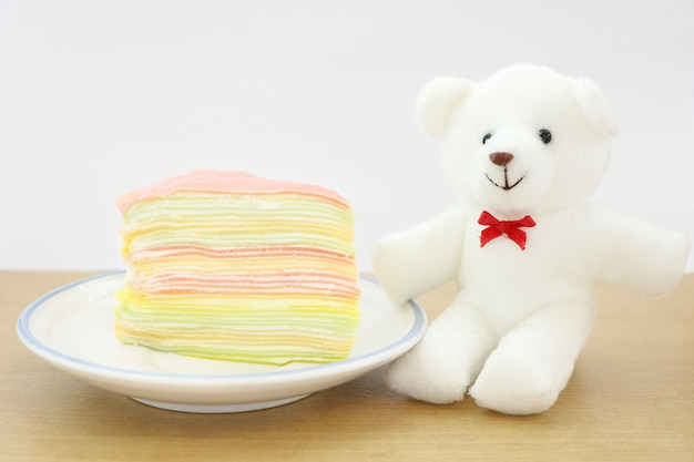 Piece of colorful crape cake dessert on white dish on wood table with white bear doll.