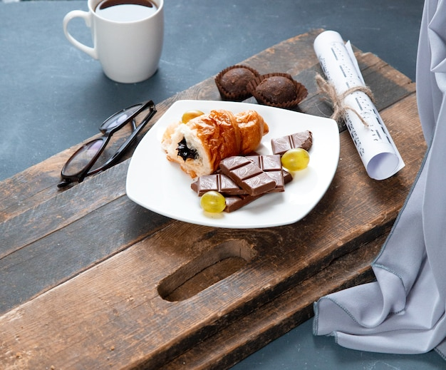 Piece of croissant and chocolate bar in a white plate with a cup of drink