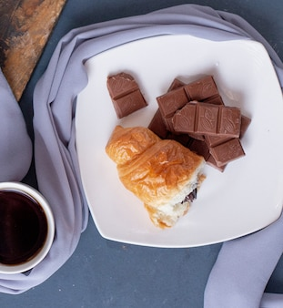 Piece of croissant and chocolate bar in a white plate