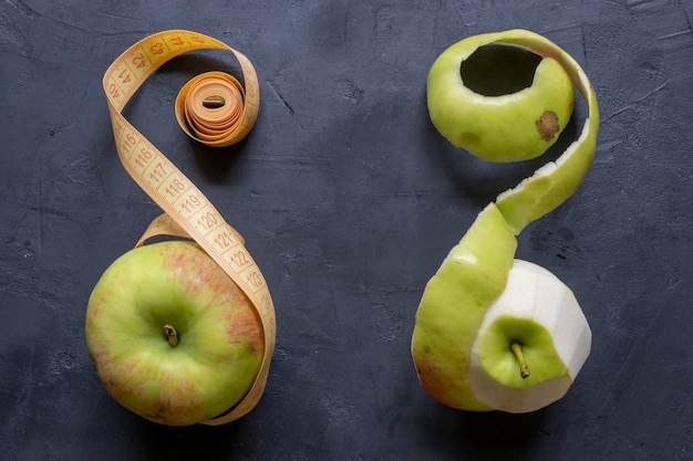 Piece of cut and peeled apple, peels and seeds, on black background.