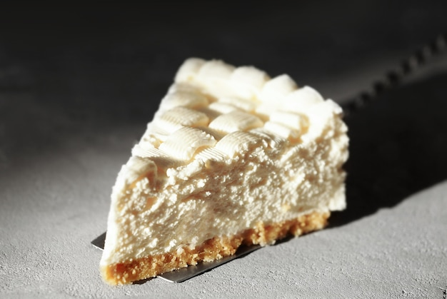 Piece of delicious cheesecake on grey table