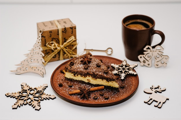 A piece of delicious chocolate cake with cream, coffee beans on a brown plate, cup of coffee is isolated on a white surface. cinnamon, anise. christmas decorations and gifts. side view.