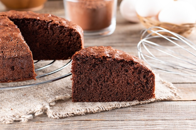 Piece of delicious fresh homemade chocolate sponge cake on wooden table