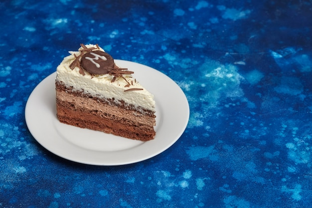 Piece of delicious mousse cake with three different kind of chocolate on white plate.