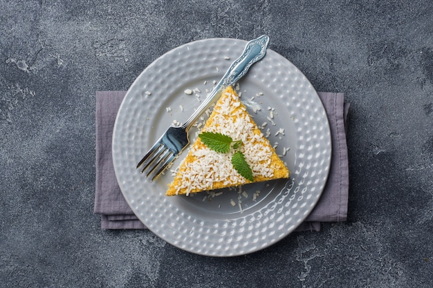 Piece of delicious puff cake with butter cream and berry jam on a plate with mint. gray concrete background. copy space.