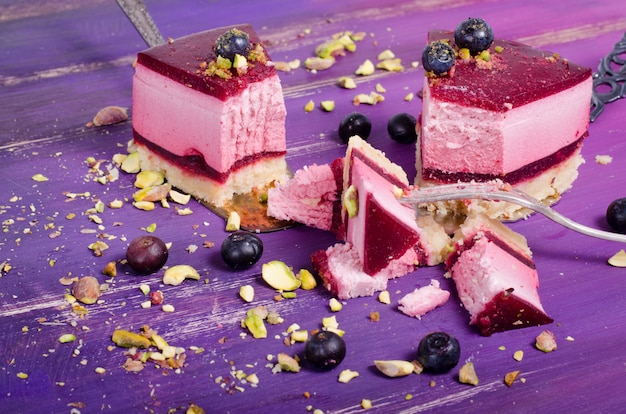 Piece of delicious raspberry cake with fresh raspberries, blueberry, currants and pistachios on shovel, bright purple, violet.
