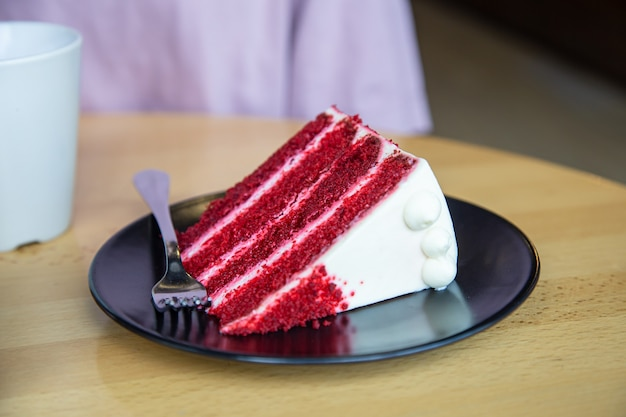 A piece of delicious red velvet cake on a plate with a fork.