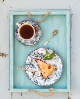 Piece of double crust plum pie and black tea in vintage porcelain cup, blue wooden tray. top view .