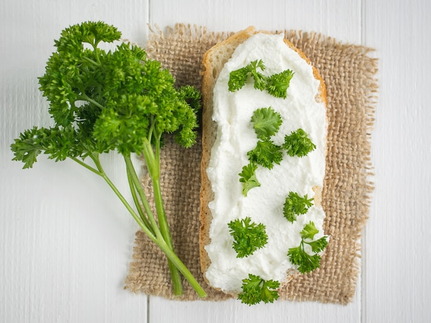 A piece of fresh bread with curd cream and a branch of parsley on a rustic table.