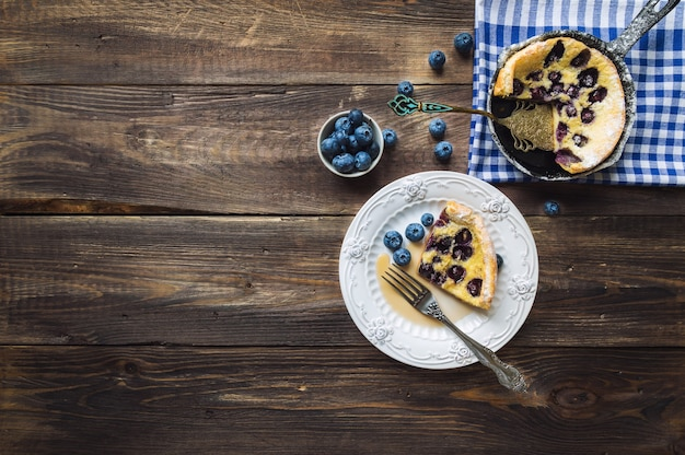 Piece of fresh homemade dutch baby pancake with blueberries on rustic wooden background