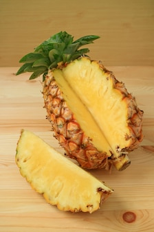 Piece of fresh ripe pineapple cut from the whole fruit isolated on wooden table