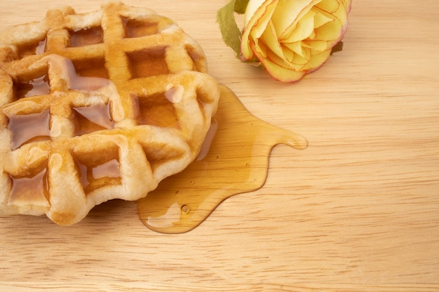 A piece of fresh waffle with honey on a wooden board.