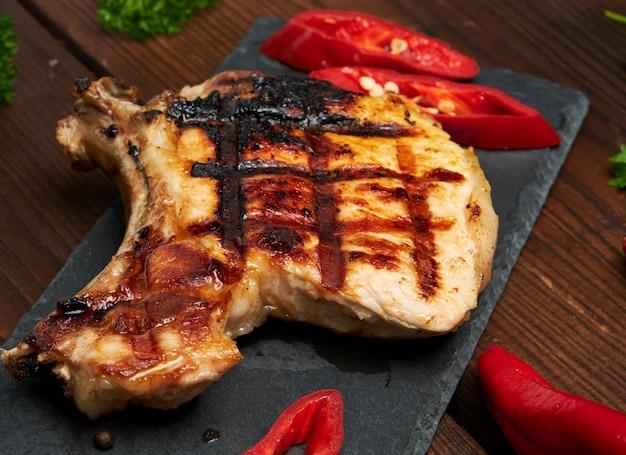 Piece of fried pork tenderloin on a bone lies on a black board