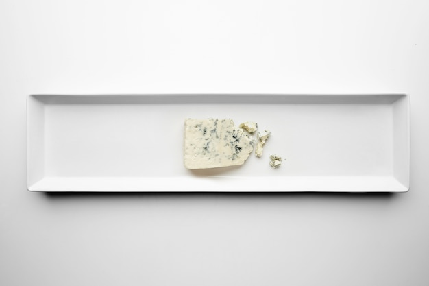 Piece of gorgonzola isolated on white plate