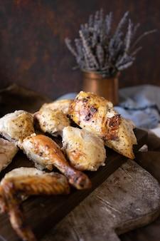 Piece of grilled chicken on dark wooden cutting board