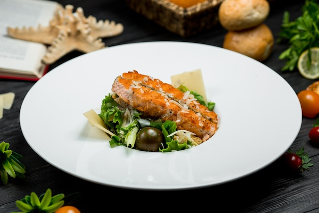 A piece of grilled salmon inside a white plate served with greenery and parmesan