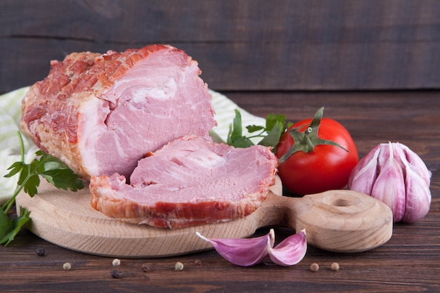 A piece of ham and vegetables on a wooden background. meatworks product