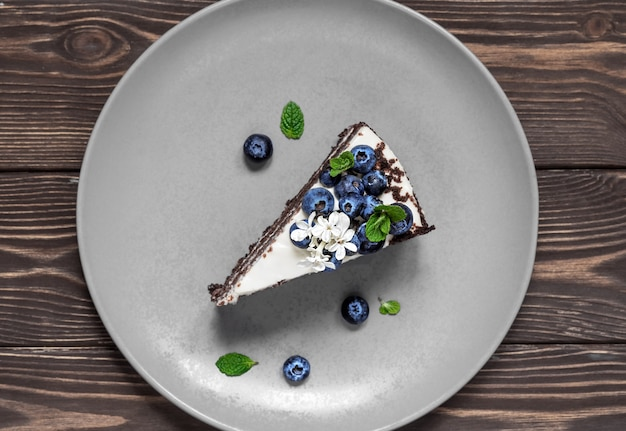 Piece of homemade bird cherry cake with sour cream, decorated with blueberries and mint leaves on a plate