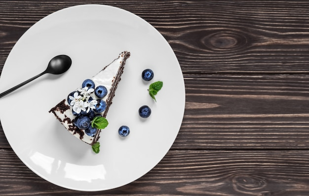 Piece of homemade bird cherry cake with sour cream, decorated with blueberries and mint leaves on a white plate