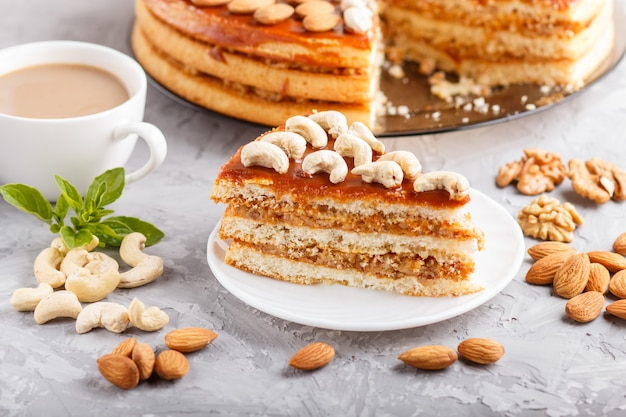 Piece of homemade cake with caramel cream and nuts on a gray concrete .