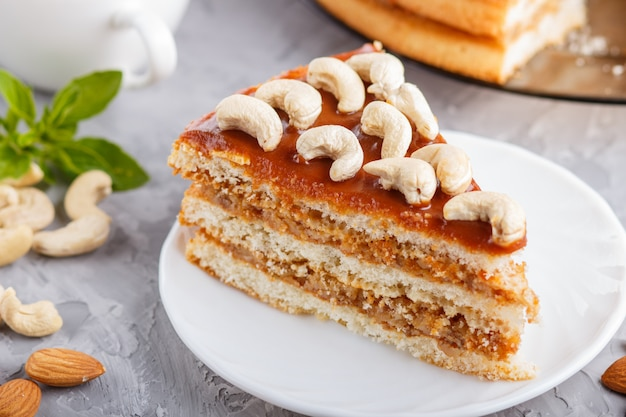 Piece of homemade cake with caramel cream and nuts with cup of coffee on gray concrete