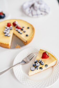 Piece of homemade cheesecake with fresh berrieson a white plate