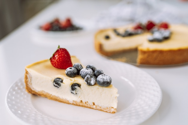Piece of homemade cheesecake with fresh strawberry and blackberry