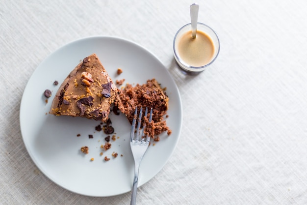 Piece of homemade chocolate cake with nuts and espresso ready to take